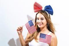 Bandiere americane felici della tenuta della giovane donna Fotografia Stock