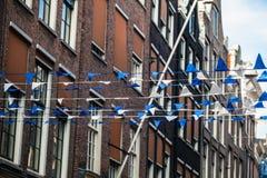 Bandiere bianco-blu colorate sulla corda contro la casa Fotografia Stock