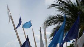 Bandiere blu che ondeggiano in vento Piccole bandiere blu triangolari che fluttuano in vento in tempo nuvoloso sulla spiaggia tro archivi video