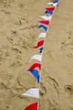 Bandiere colorate della stamina sulla superficie della sabbia Fotografie Stock Libere da Diritti