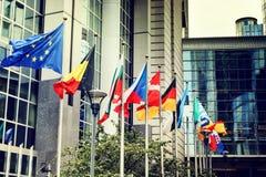 Bandiere d'ondeggiamento davanti alla costruzione del Parlamento Europeo a Brussel Immagine Stock Libera da Diritti
