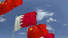 Bandiere d'ondeggiamento del Bahrain e della Cina sul fondo del cielo, animazione loopable 3D archivi video