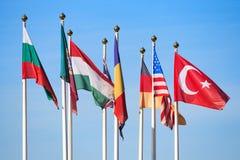 Bandiere dei paesi differenti contro un cielo blu Fotografie Stock Libere da Diritti