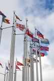 Bandiere dei paesi differenti sul fondo del cielo nuvoloso Immagine Stock