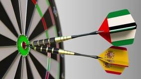 Bandiere dei UAE e della Spagna sui dardi che colpiscono centro dell'obiettivo Cooperazione internazionale o concorrenza concettu stock footage