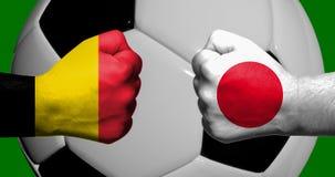 Bandiere del Belgio e del Giappone dipinti su un affronto di due pugni chiusi Fotografia Stock Libera da Diritti