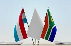 Bandiere del Lussemburgo e della Repubblica Sudafricana fotografia stock libera da diritti