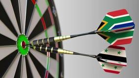 Bandiere del Sudafrica e della Siria sui dardi che colpiscono centro dell'obiettivo Cooperazione internazionale o concorrenza stock footage