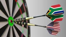 Bandiere del Sudafrica e U.S.A. sui dardi che colpiscono centro dell'obiettivo Cooperazione internazionale o concorrenza archivi video