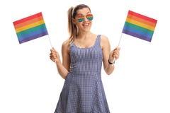 Bandiere dell'arcobaleno della tenuta della giovane donna Fotografia Stock