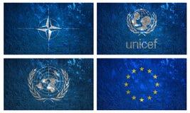 Bandiere dell'UNICEF, della NATO, della nazione unita e dell'EURO Immagini Stock