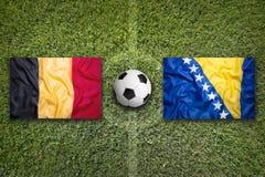 Bandiere della Bosnia-Erzegovina e del Belgio sul campo di calcio Immagine Stock