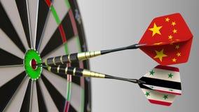 Bandiere della Cina e della Siria sui dardi che colpiscono centro dell'obiettivo Cooperazione internazionale o concorrenza concet stock footage