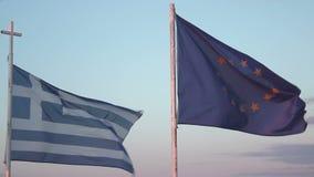 Bandiere della Grecia e dell'UE che ondeggiano in vento contro il fondo del cielo blu, crisi di debito stock footage