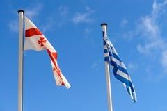 Bandiere della Grecia e di Georgia sui precedenti del cielo Immagine Stock Libera da Diritti