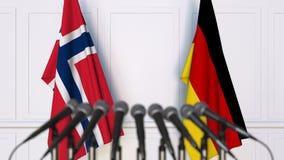 Bandiere della Norvegia e della Germania alla riunione o alla conferenza internazionale rappresentazione 3d Immagine Stock