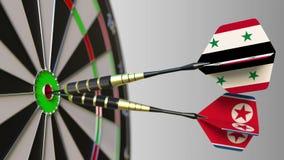 Bandiere della Siria e della Corea del Nord sui dardi che colpiscono centro dell'obiettivo Cooperazione internazionale o concorre video d archivio