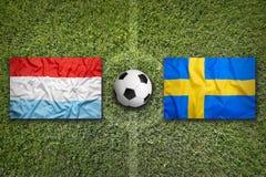 Bandiere della Svezia e del Lussemburgo sul campo di calcio Immagine Stock