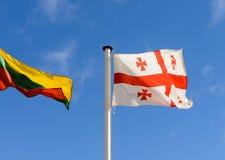 Bandiere di Georgia e della Lituania sui precedenti del cielo Immagini Stock Libere da Diritti