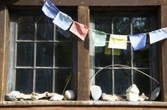 Bandiere di preghiera, raccolta della roccia e vetri di finestra antiquati Fotografie Stock Libere da Diritti