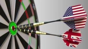 Bandiere di U.S.A. ed il Regno Unito sui dardi che colpiscono centro dell'obiettivo Cooperazione internazionale o Immagini Stock Libere da Diritti