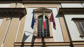 Bandiere italiane ed europee dell'università, che ondeggiano sopra l'entrata dell'università di Pavia, Italia video d archivio