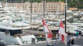 Bandiere nazionali di sbattimento del Monaco in vento, yacht club di lusso defocused in porto video d archivio