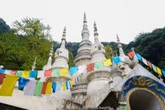 Bandiere pregare variopinte sulla pagoda antica sul fianco di una montagna Immagini Stock Libere da Diritti