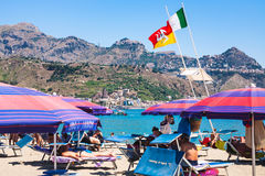 Bandiere sopra la gente sulla spiaggia urbana di Giardini Naxos Fotografia Stock Libera da Diritti