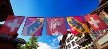 Bandiere svizzere nel vecchio centro urbano della città di Gstaad, stazione sciistica famosa Fotografia Stock