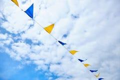 Bandiere triangolari gialle e blu di festival sul fondo del cielo con le nuvole bianche Partito all'aperto di celebrazione festiv immagini stock libere da diritti