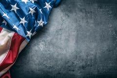 Bandierina degli S Bandiera americana Bandiera americana che si trova liberamente sul fondo concreto Colpo dello studio del primo Immagini Stock Libere da Diritti