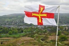 Bandierina di Guernsey sopra il paesaggio britannico Immagini Stock