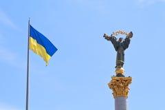 Bandierina e monumento ucraini a Berehynia a Kiev fotografie stock