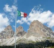 Bandierina italiana davanti alle montagne della dolomia Fotografia Stock