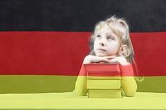 Bandierina tedesca la ragazza bionda vuole imparare tedesco Doppia esposizione immagini stock libere da diritti