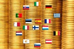 Bandierine dei paesi di eurozone contro i mucchi delle monete Fotografie Stock Libere da Diritti