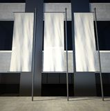 bandierine di pubblicità vuote in bianco 3d sulla parete della costruzione Immagine Stock