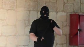 Bandiet in balaclava die met lus in een hinderlaag lokken stock video