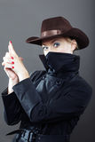 Bandit. Vertical photo of the gangster lady with cowboy hat on a gray background Stock Photography