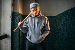 Bandit avec la batte de baseball se tenant dans l'entrée photos stock