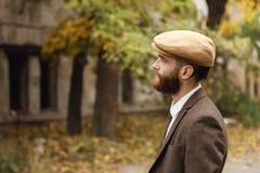 Bandit avec une barbe regardant fixement dans la distance se tenant près d'un bâtiment abandonné rétro outdoors Images libres de droits