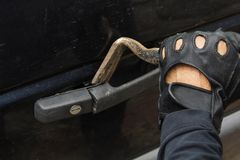 Bandit in black gloves breaking in car lock with crowbar tool. royalty free stock photography