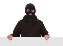 Bandit In Black Mask With Blank Card. Man Wearing Mask Holding A Blank Card Over White Background Royalty Free Stock Photography
