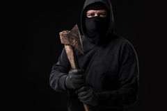 Bandit in black mask with hatchet on black background. Masked man with an ax Stock Image
