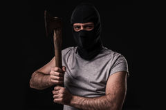 Bandit in black mask with hatchet on black background. Masked man with an ax Stock Photo