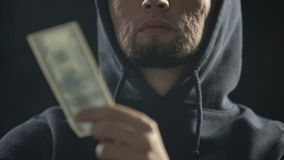 Bandit dangereux jugeant l'argent dans la chambre noire plein de la fumée, paiement pour le crime banque de vidéos