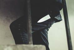 Bandit, der eine Maske geht auf Treppe mit einem Messer für die Beute trägt stockfotografie