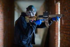 Bandit in der schrecklichen Maske mit Gewehr stockfotografie