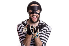 Bandit showing stolen jewelry and smiling Royalty Free Stock Image